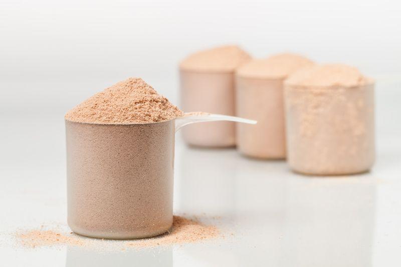 Ein Löffel Whey Protein Isolat Schokolade ohne Aspartam mit drei Löffeln im Hintergrund