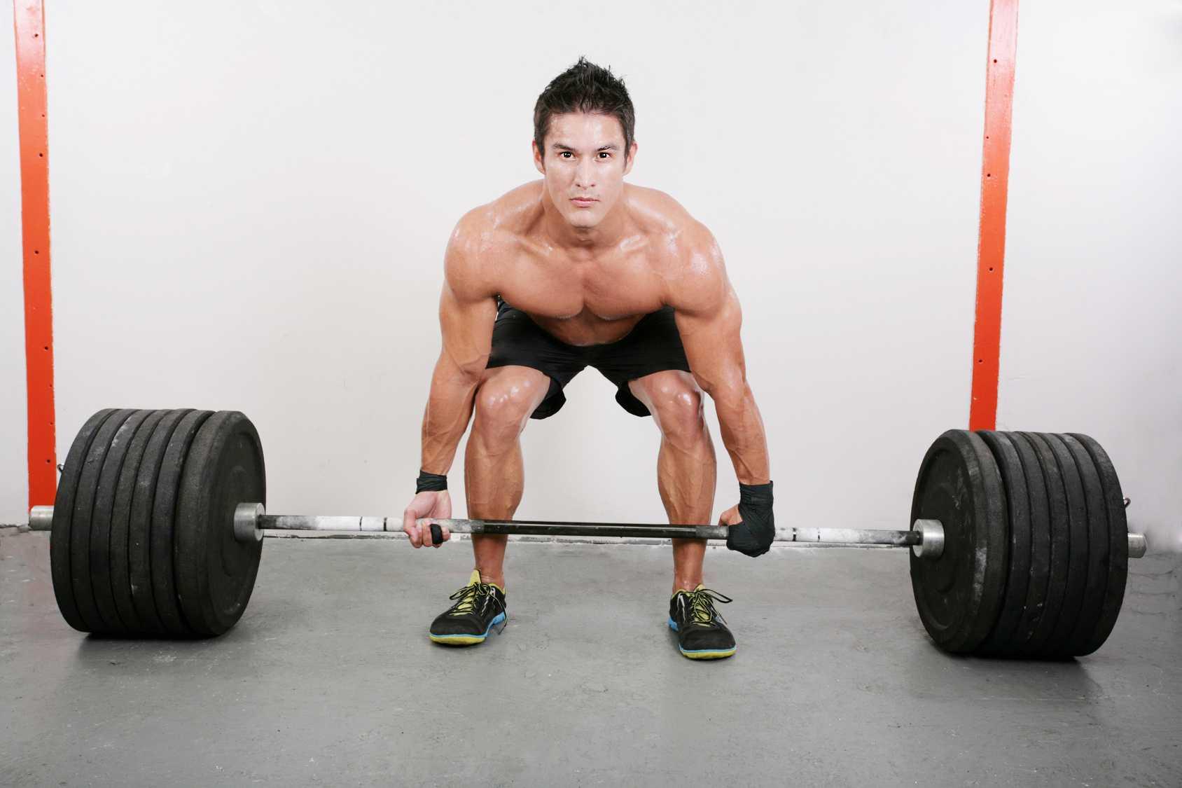 Muskulöser Mann macht eine der Grundübungen mit 200 kg (Kreuzheben)